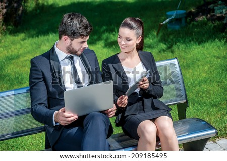 Share the results of work. Successful businessman with laptop and business woman with tablet work outside the office. Woman showing the results of the tablet - stock photo