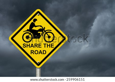 Share the Road Warning Sign, An road warning sign with words Share the Road and a motorcycle icon with stormy sky background - stock photo