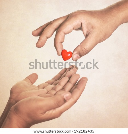 Share your love (hand giving a heart in vintage style) - stock photo