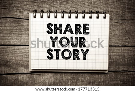 Share your story written on the paper on a wood background - stock photo