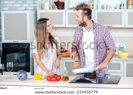 Shared cooking food. Young and beautiful couple in love preparing meals in the kitchen and look at each other while standing in the kitchen - stock photo