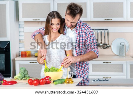 Shared cooking. Young and beautiful loving couple and help each other while preparing dinner with vegetables in the kitchen. - stock photo