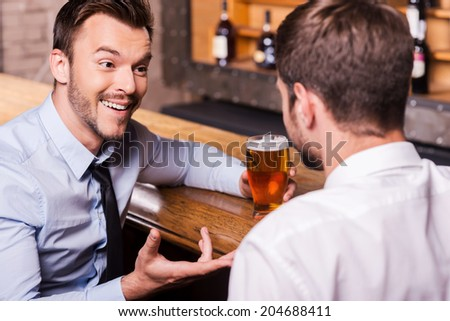 Sharing beer with good friend. Two cheerful young men in shirt and tie talking to each other and gesturing while drinking beer at the bar counter  - stock photo