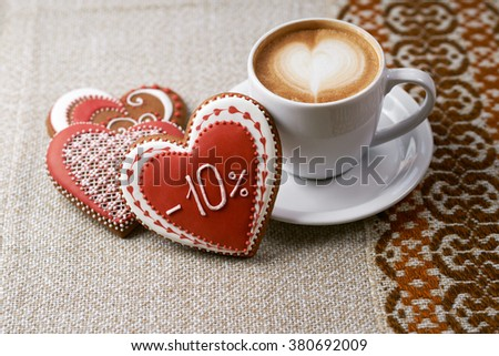 Sharing delicious. Top view shot of gingerbread heart shaped Valentines day cookies and a cup of coffee with froth design - stock photo