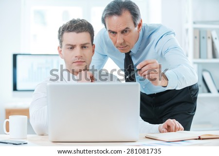 Sharing experience with colleague. Two serious business people in formalwear discussing something and looking at laptop  - stock photo