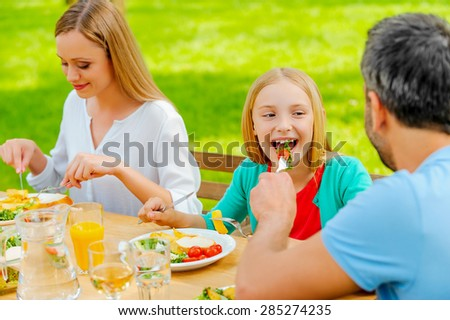 Sharing food with the nearest. Young man feeding his daughter with salad while sitting together at the dining table outdoors