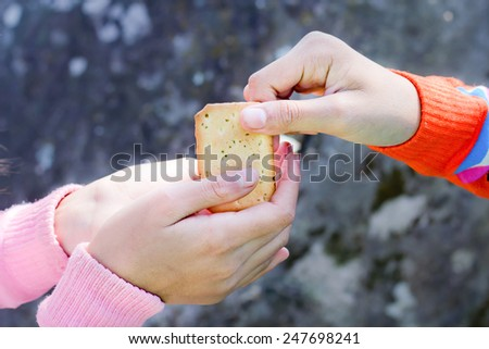 Sharing food. Women giving a cracker to a small child. Charity concept. - stock photo