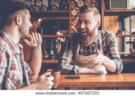 Sharing good news. Barista and his customer discussing something with smile while sitting at bar counter at cafe - stock photo