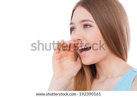 Sharing good news. Side view of cheerful teenage girl shouting and holding hand near mouth while standing isolated on white - stock photo