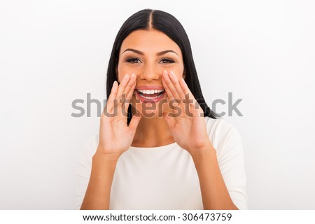 Sharing good news. Smiling young woman holding hands near her mouth and looking at camera while standing against white background - stock photo