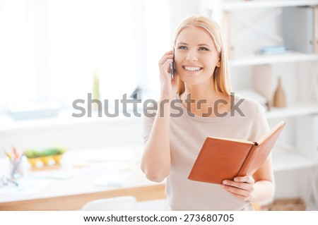 Sharing good news with colleagues. Beautiful young woman talking on the mobile phone and holding note pad while standing near her working place in office - stock photo