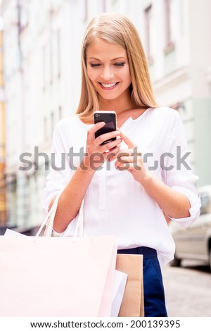 Sharing good news with friend. Close-up of beautiful young smiling woman holding shopping bags and mobile phone while standing outdoors - stock photo