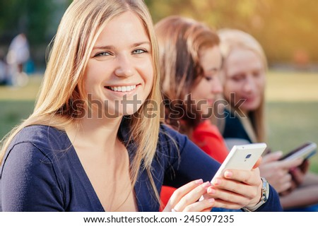 Sharing good news with friends. Cheerful young woman holding a mobile phone and smiling while group of people communicating on background out of focus - stock photo
