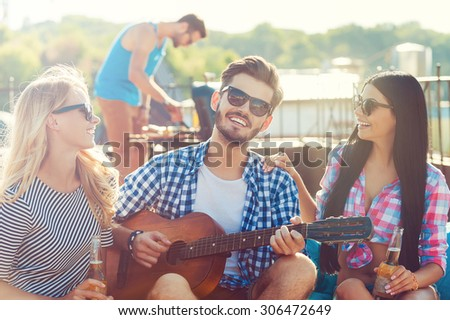 Sharing good time. Three cheerful young people bonding to each other and sitting on the bean bag with guitar while man barbecuing in the background - stock photo