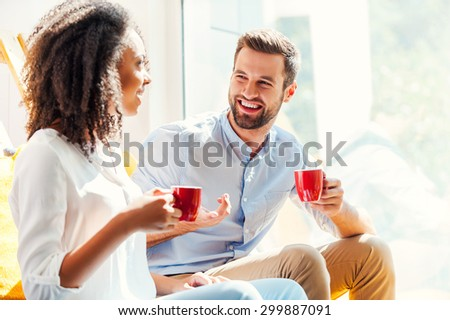 Sharing great ideas. Happy young African woman and young man holding cups of coffee and discussing something while sitting together near the window  - stock photo