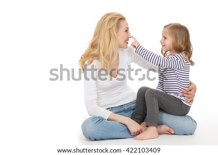Sharing happy moments. Studio shot of a little girl sitting on a leg of her mother touching her nose with her finger isolated on white.