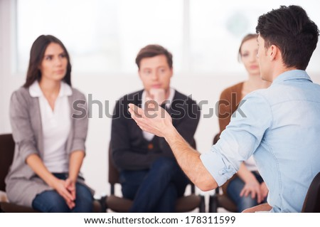 Sharing his problems with people. view of man telling something and gesturing while group of people sitting in front of him and listening - stock photo