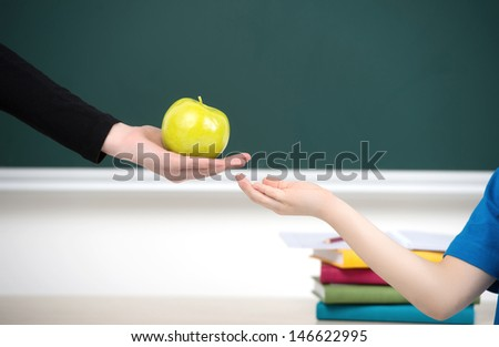 Sharing is good. Close-up of teacher giving an apple to the kid - stock photo