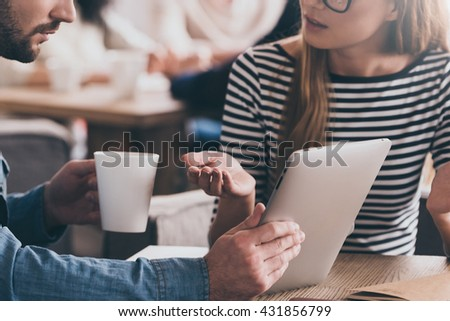 Sharing news in cafe. Close-up of young beautiful woman gesturing and looking at man holding digital tablet  - stock photo