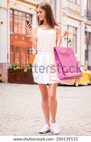 Sharing news with friends. Full length of beautiful young smiling woman holding shopping bags and looking at her mobile phone while standing outdoors - stock photo