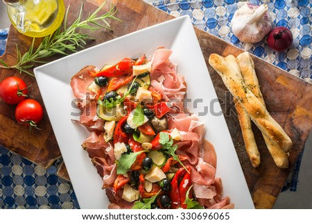sharing platter with Italian ham pizza sticks and vegetables - stock photo