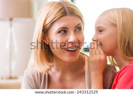 Sharing secrets with mom. Happy mother and daughter sharing secrets while sitting at home together - stock photo