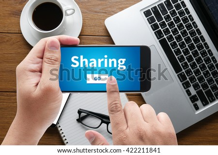 Sharing (Sharing Share Social Networking Connection Communication ) message on hand holding to touch a phone, top view, table computer coffee and book