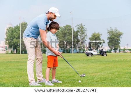 Sharing with golf experience. Cheerful young man teaching his son to play golf while standing on the golf course - stock photo