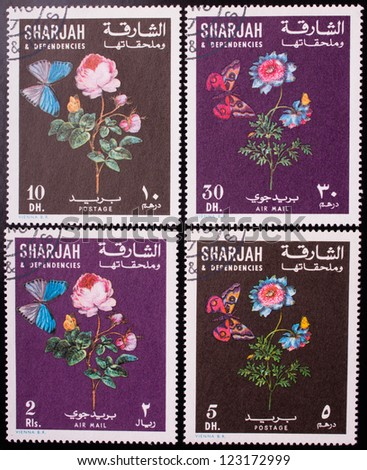 SHARJAH - CIRCA 1970: A stamp printed in Sharjah shows  four kinds of flowers and butterflies , circa 1970. - stock photo