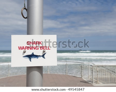 Shark Warning Bell sign and Bell Ringer at St Clair Beach, Dunedin, New Zealand - stock photo
