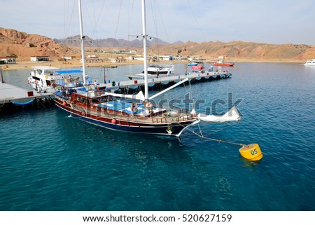 SHARM EL SHEIKH, EGYPT -  DECEMBER 4: The sail yacht with tourists is near pier in harbor of Sharm el Sheikh. It is popular tourists destination on December 4, 2013 in Sharm el Sheikh, Egypt