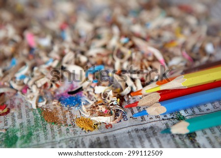 Sharp colored pencils lie on an old paper. Around there are a lot of chips - stock photo