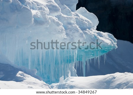 sharp cyan icicles overhanging snow - stock photo