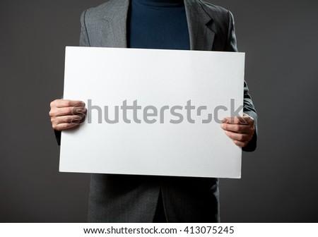 Sharp dressed man holding white blank billboard - stock photo