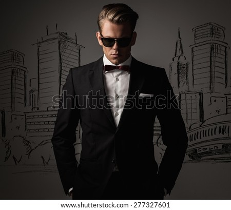 Sharp dressed man in black suit against city panorama drawing - stock photo