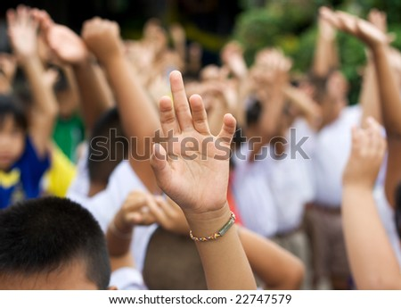 sharp hand raised in blury schoolyard background