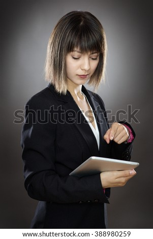 sharp looking business woman using a tablet computer shot in the studio low key lighting on a gray background - stock photo