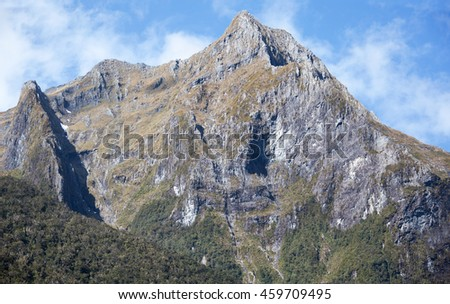 Sharp peaks of mountains that surround Milford Sound in Fiordland National Park (New Zealand).