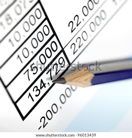 Sharp pencil resting on page of financial figures.  Angled view, with focus on tip of pencil.