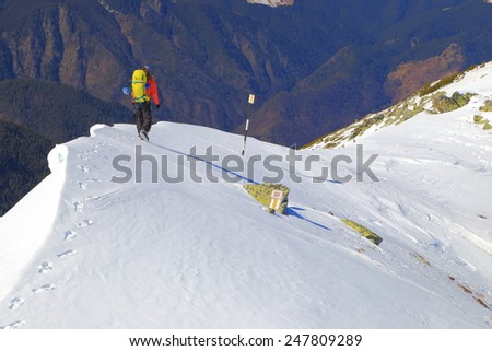 Sharp snowy ridge and remote climber in sunny winter day
