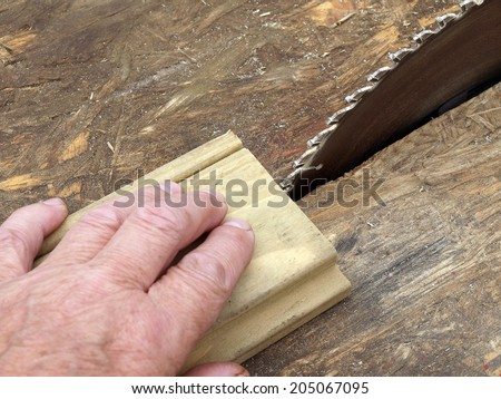 Sharp toothed circular saw disk and worker`s hand close up - stock photo