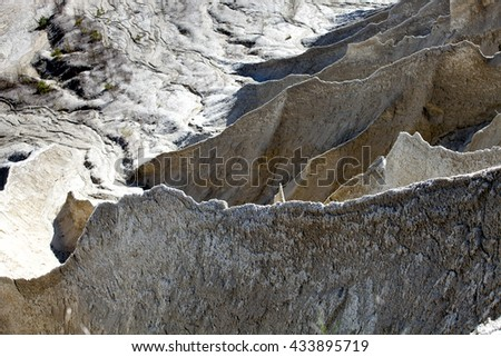 Sharp unusual water eroded terrain of large mining Spoil tip hill - stock photo