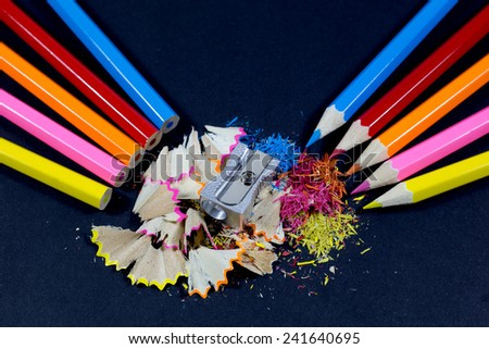 Sharpened Colorful Pencils Against Blunt Pencils with Metallic Pencil Sharpener and Colorful Pencil Shavings on Black Background - stock photo