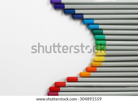 Sharpened monochrome watercolor pencils with multicolor slate-pencil on a white background with space for your title text  - stock photo