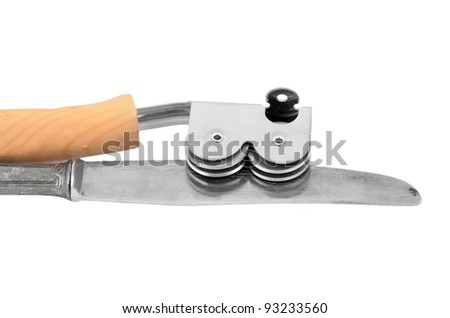 Sharpening a knife with a knife grinder on white background - stock photo