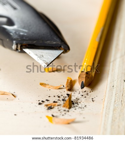 Sharpening a pencil with box cutter - stock photo