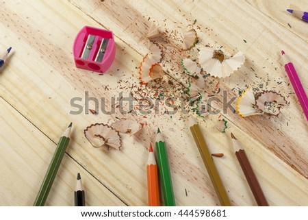 Sharpening a selection colouring pencils on a wooden desk with a pink pencil sharpener - stock photo