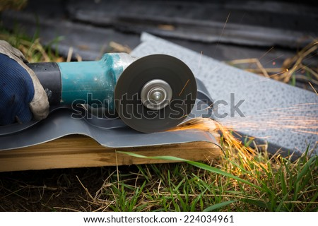 sharpening and cutting of iron by abrasive disk machine - stock photo