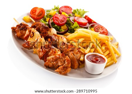 Shashlik - grilled meat, chips and vegetables  - stock photo