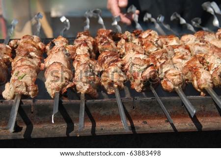 Shashlik (shaslik) - traditional russian barbecue. Pork Shish kebab on Fire. Appetizing fresh meat shish kebab prepared on a grill wood coal, outdor - stock photo
